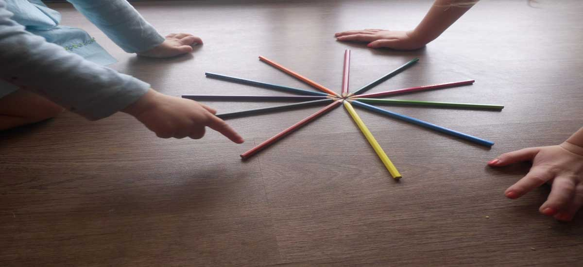 Child Psychotherapy, picture of children playing on the floor, pencil on the floor